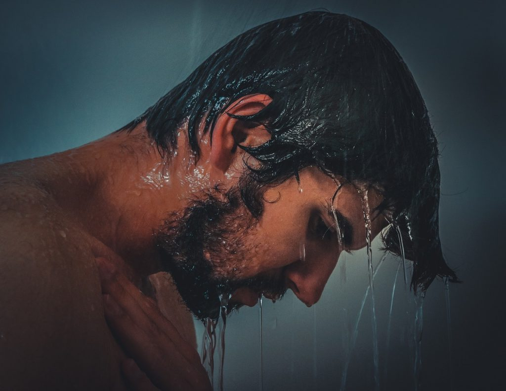 Man washing hair in a shower