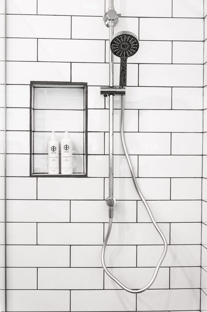 Shower on bathroom wall with insert holding hair products